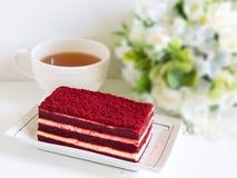 Bolo vermelho de veludo e um copo do chá imagens de stock