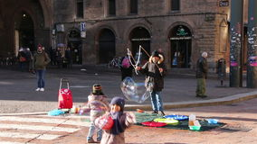 Bologna, Italy - January 1, 2015 Children Amazed By Huge Soap Bubbles On The Street in Bologna, Italy.Street Art. stock video