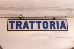 Trattoria sign hanging from the ceiling in the street royalty free stock photography