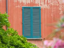 Bologna, Italy - Red wall and window. A weathered red wall and window with green wooden shutters in Bologna, Italy royalty free stock photo