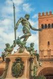 Bologna Neptune fountain. Of Bologna city in Emilia region of Italy. Restored Nettuno bronze statue, with historic orange-red tower buildings background in stock photo