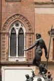 Bologna, Neptune's bronze statue and window. Bologna (Emilia-Romagna, Italy) Neptune's bronze statue (Gianbologna, 1565) and historic palace facade stock photos