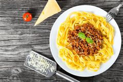 Bolognese ragout with italian pasta on a white plate, decorated with basil leaves, authentic recipe, wooden background with celery Royalty Free Stock Photos