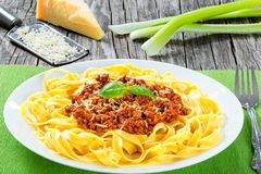 Bolognese ragout with italian pasta on a white plate, decorated with basil leaves, authentic recipe, wooden background with celery Stock Photo