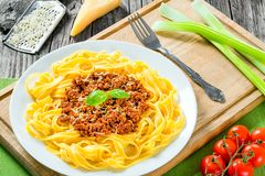 Bolognese ragout with italian pasta on a white plate, decorated with basil leaves, authentic recipe, wooden background with celery Stock Images