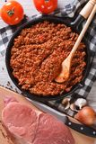 Bolognese sauce in pan and ingredients vertical top view closeup. Bolognese sauce in a skillet with the ingredients on the table. vertical top view closeup Royalty Free Stock Image