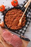 Bolognese sauce in skillet with ingredients vertical top view. Bolognese sauce in a skillet with the ingredients on the table. vertical top view closeup Royalty Free Stock Photos