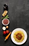 Bolognese spagetti och dess ingredienser på den svarta bakgrunden Royaltyfri Foto