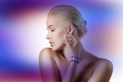 Bolond girl make up with gem stone. Very cute blond young woman with hair style with some shining gem stone on her eyes as a creative make up Royalty Free Stock Photos