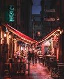BOLONHA, ITÁLIA - 15 DE FEVEREIRO DE 2016: Os povos não identificados estão andando em uma rua com restaurantes e barras na Bolon fotografia de stock royalty free
