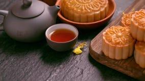 Bolos bonitos da lua em uma bandeja de madeira com chá e na flor no fundo preto da ardósia Festival tradicional chin?s do Meados  video estoque