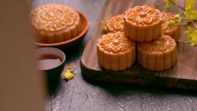 Bolos bonitos da lua em uma bandeja de madeira com chá e na flor no fundo preto da ardósia Festival tradicional chin?s do Meados  filme
