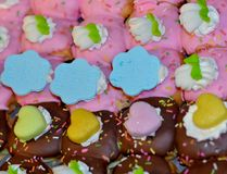 Bolos cobertos com o chocolate, geada cor-de-rosa com creme branco Foto de Stock