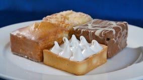 Bolos com cereja em uma placa branca em placas de madeira Pastelarias diferentes bolos Imagem de Stock