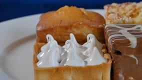 Bolos com cereja em uma placa branca em placas de madeira Pastelarias diferentes bolos Imagens de Stock