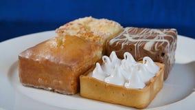 Bolos com cereja em uma placa branca em placas de madeira Pastelarias diferentes bolos Imagens de Stock Royalty Free