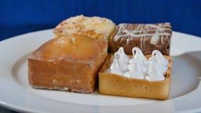 Bolos com cereja em uma placa branca em placas de madeira Pastelarias diferentes bolos Foto de Stock Royalty Free