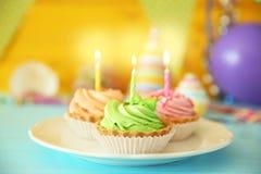Bolos de aniversário deliciosos com velas no fundo festivo Fotografia de Stock Royalty Free