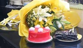 Bolos de aniversário saborosos dos pedaços de chocolate e da morango com o ramalhete envolvido bonito da flor Foto de Stock