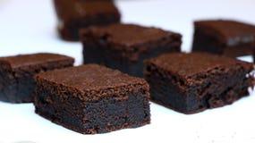 Bolos de chocolate: brownies muito pretas do chocolate em uma placa branca Fotografia de Stock