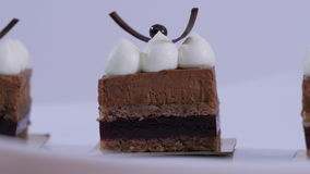 Bolos de chocolate na placa branca com creme de chicoteamento Musse de chocolate da sobremesa com fim do chantiliy acima filme