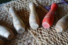 Bolos de madera viejos, jugados en épocas medievales, en un contexto áspero de la arpillera Uno de ellos es rojo Foto de archivo