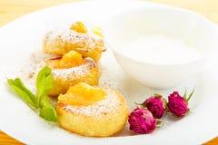 Bolos de queijo em uma placa branca com creme de leite Imagem de Stock