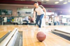 Bolos del adolescente en club con el foco en la bola de Brown Imágenes de archivo libres de regalías