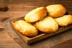 Bolos do fermento com queijo, pastelaria tradicional do russo, no fundo de madeira Imagem de Stock Royalty Free