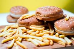 Bolos do hamburguer com batatas fritas no fundo de madeira Fotografia de Stock Royalty Free