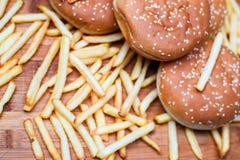 Bolos do hamburguer com batatas fritas no fundo de madeira Imagem de Stock