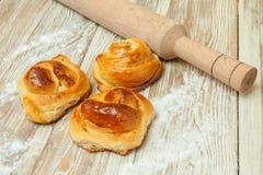 Bolos do trigo, rolos com canela, rolamento-pino, refeição na tabela Imagem de Stock
