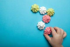 Bolos doces, pairosos da merengue em um fundo azul A mão de uma criança guarda um O conceito de um feriado das crianças, o dia de imagens de stock