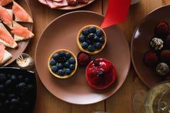 Bolos frescos deliciosos do mirtilo e da morango na tabela do feriado fotos de stock royalty free