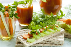 Bolos lisos do centeio, centeio do galette com cenouras frescas, aipo e salsa em torno do suco de cenoura fresco Foto de Stock Royalty Free
