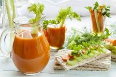 Bolos lisos do centeio, centeio do galette com cenouras frescas, aipo e salsa em torno do suco de cenoura fresco, cenoura fresca  Foto de Stock Royalty Free