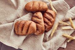 Bolos recentemente cozidos e spikelets do trigo que encontram-se em um pano de linho imagens de stock royalty free