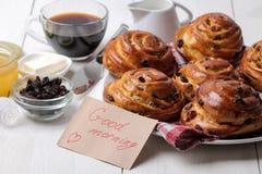 Bolos saborosos com passas e café com leite em um fundo de madeira branco Padaria fresca Pequeno almoço foto de stock