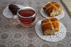 Bolos transversais quentes, copo do chá e ovos de chocolate na tabela de easter Fotografia de Stock Royalty Free