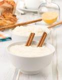 Bols débordants de riz au lait, sur le bois Photos stock