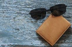bolsa de couro com os óculos de sol que encontram-se em uma tabela de madeira imagens de stock