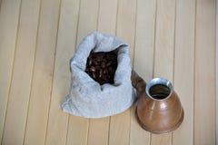 Bolsa de los granos de café con un pote que prepara turco imagen de archivo