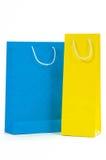 Bolsa de papel amarillo y azul aislada en el fondo blanco Foto de archivo libre de regalías