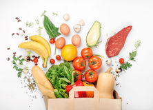 Bolsa de papel llena de diversa comida sana en el fondo blanco Foto de archivo libre de regalías