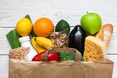 Bolsa de papel llena de diversa comida vegetariana sana en el fondo de madera blanco Fotografía de archivo