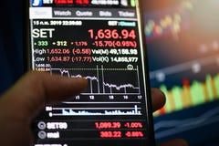 A bolsa de valores da aplicação de Tailândia no smartphone com o indicador das cartas do gráfico fotografia de stock royalty free