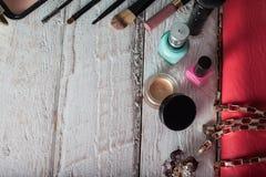 Bolsa fêmea com cosméticos e móbil na madeira branca imagens de stock