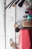 Bolsa fêmea com cosméticos e móbil na madeira branca fotografia de stock royalty free