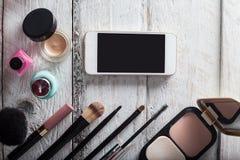 Bolsa fêmea com cosméticos e móbil na madeira branca fotos de stock royalty free