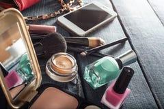 Bolsa fêmea com cosméticos e móbil no fundo das calças de brim fotografia de stock